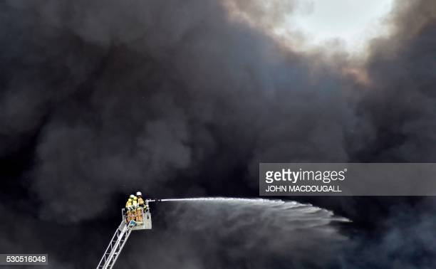 TOPSHOT Firemen on a ladder are engulfed in smoke as they douse a fire in a storage facility with water at the Dong Xuan shopping centre in Berlin's...