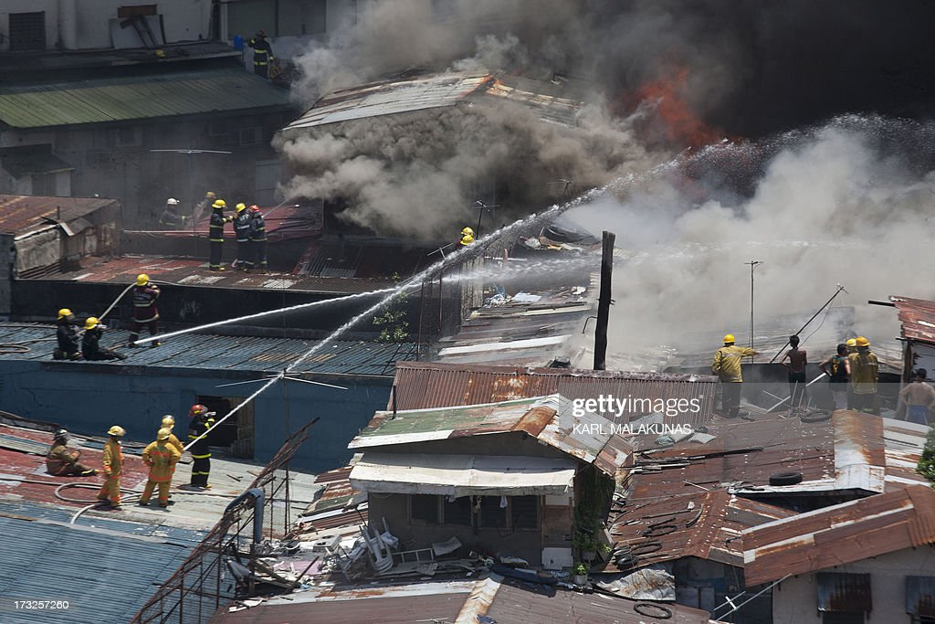 Firemen on top of corrugated rooves extinguish a fire that engulfed a shanty town in the financial district of Manila on July 11, 2013. There were no immediate reports of casualties from the blaze, which occurred mid-morning amid government plans to relocate thousands of families living in areas vulnerable to floods and typhoons.