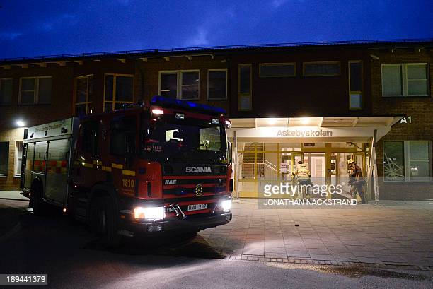 Firemen open the doors of a school in the Stockholm suburb of Tensta after extinguishing a burning room after youths rioted in few different suburbs...