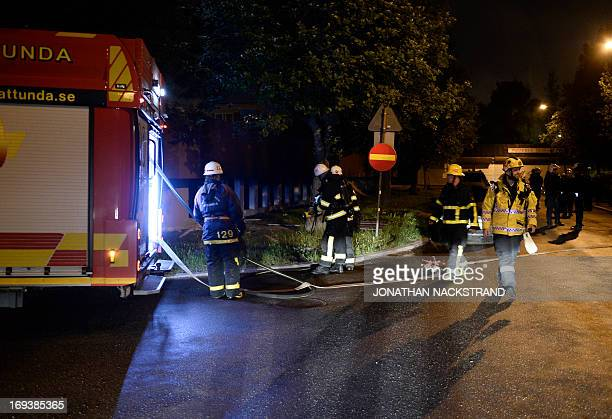 Firemen pack their gear after extinguishing a burning car parking in an indoor garage in the Stockholm suburb of Tureberg after youths rioted in...