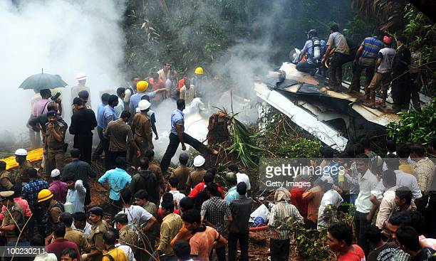 Firemen paramilitary personnnel and onlookers gather at the site of a plane crash on May 22 2010 in Mangalore An Air India Express Boeing 737800...