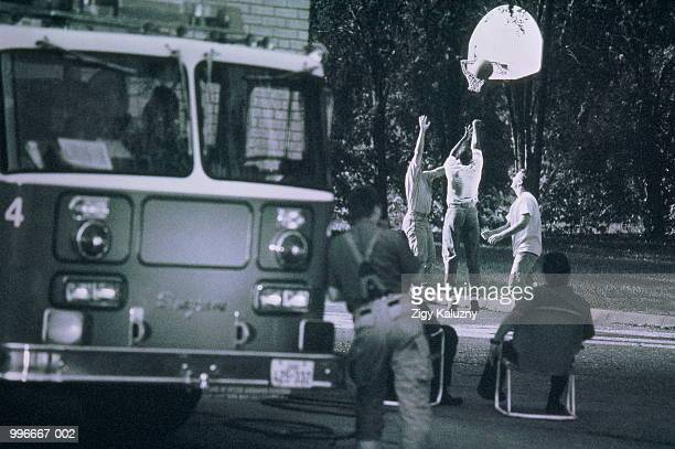 Firemen playing basketball during break,fire truck in foreground(B&W)