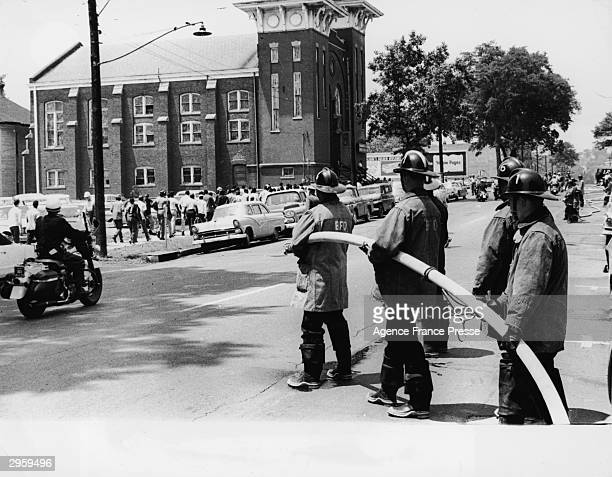 Firemen prepare to use hoses to suppress AfricanAmerican demonstrators on the far side of the street during race riots in Birmingham Alabama early...
