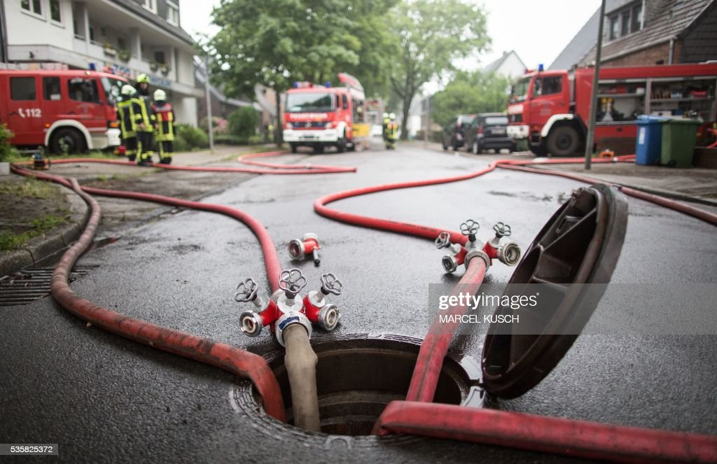 Firemen pump out basements of apartment buildings in Oberhausen, western Germany, after a thunderstorm on May 30, 2016. Four people died and several more were injured in southern Germany after violent storms with torrential rains caused severe flooding, authorities said. / AFP / dpa / Marcel Kusch / Germany OUT
