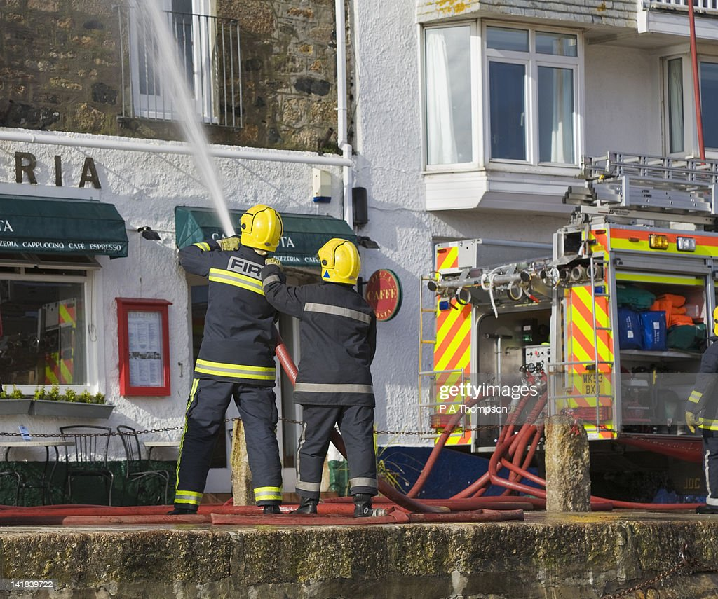 Firemen putting out building fire, St Ives, Cornwall, England : Stock Photo