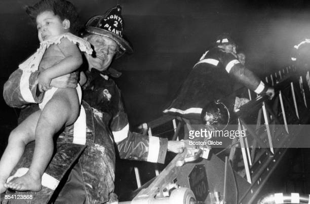 Firemen rescue children from a fire on Dudley and Greenville Street in the Roxbury neighborhood of Boston March 4 1974