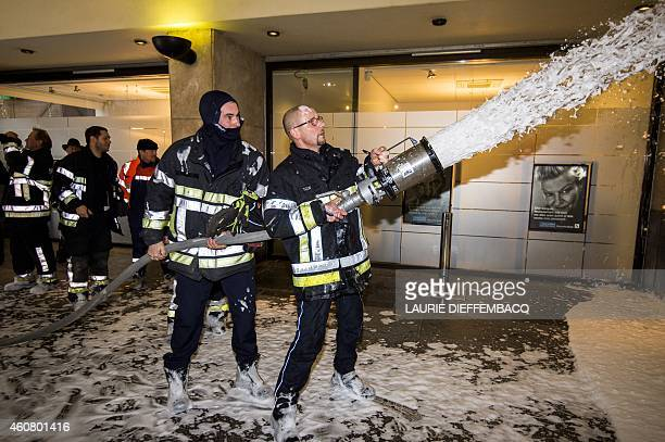 Firemen spray firefighting foam into the Namur city hall during a protest action on December 23 2014 AFP PHOTO / BELGA PHOTO LAURIE DIEFFEMBACQ