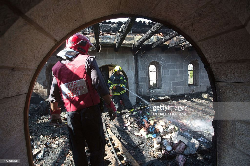 Firemen spray water on debris at a room located on the complex of the Church of the Multiplication at Tabgha on the shores on the Sea of Galilee in...