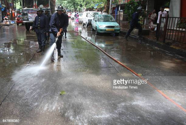 Firemen spray water to clean the spilled oil by vehicle on the road agar bazar near Siddhivinayak on thursday