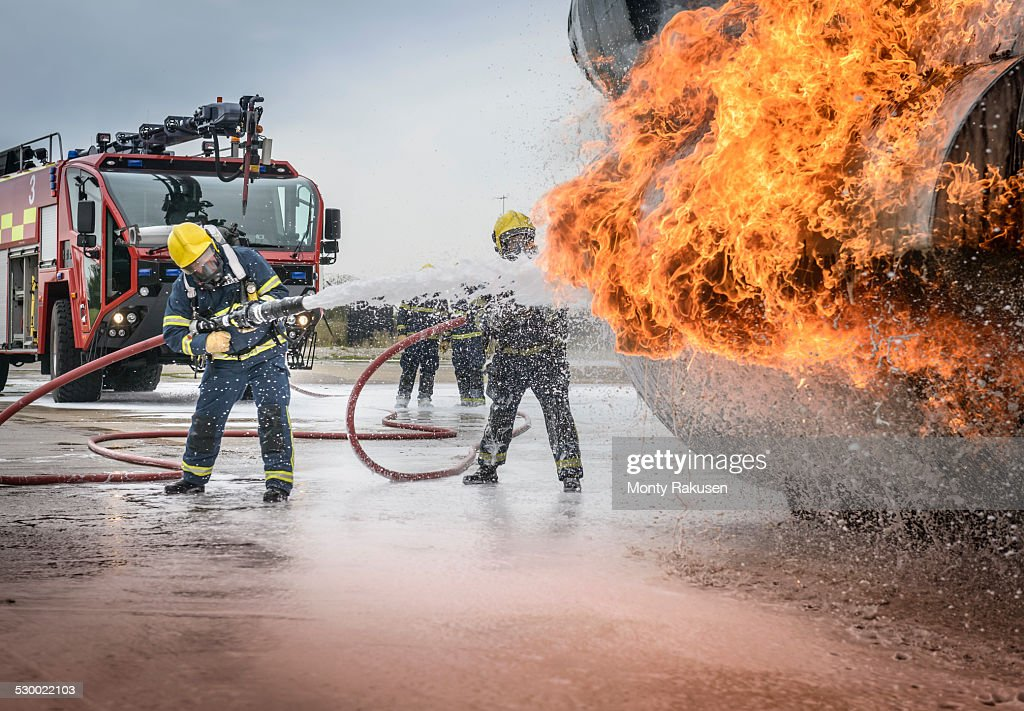 Firemen spraying water on simulated aircraft fire at training facility : Stock Photo