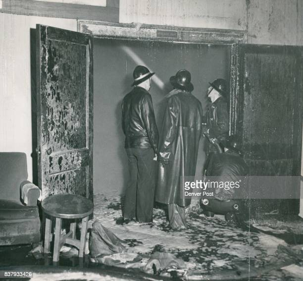 Firemen stand ankledeep in water as they battle the blaze at the door of the gymnasium on the second floor of the Denver Athletic dub The disastrous...
