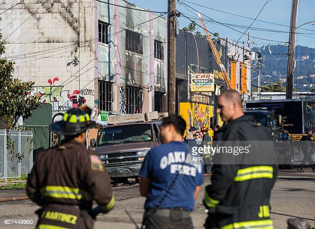 Firemen stand near a warehouse after it was destroyed by a fire December 3 2016 in Oakland California Up to 40 people were feared dead in a huge fire...