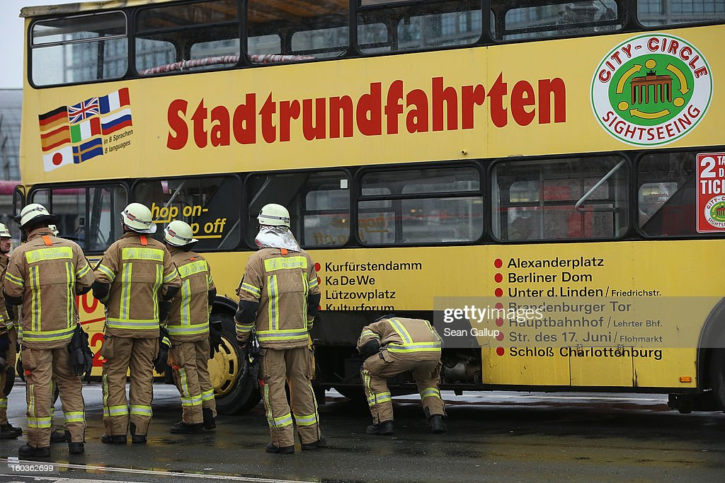 Firemen stand next to a bus of City Circle Sightseeing after its heating unit overheated and began smoking on January 30, 2013 in Berlin, Germany. No one was injured.