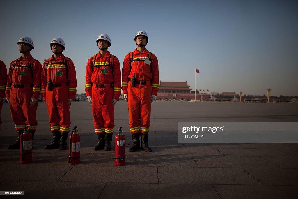 Firemen stand on Tiananmen Square during the opening session of the Chinese People's Political Consultative Conference (CPPCC) at the Great Hall of the People in Beijing on March 3, 2013. Thousands of delegates from across China meet this week to seal a power transfer to new leaders whose first months running the Communist Party have pumped up expectations with a deluge of propaganda. AFP PHOTO / Ed Jones