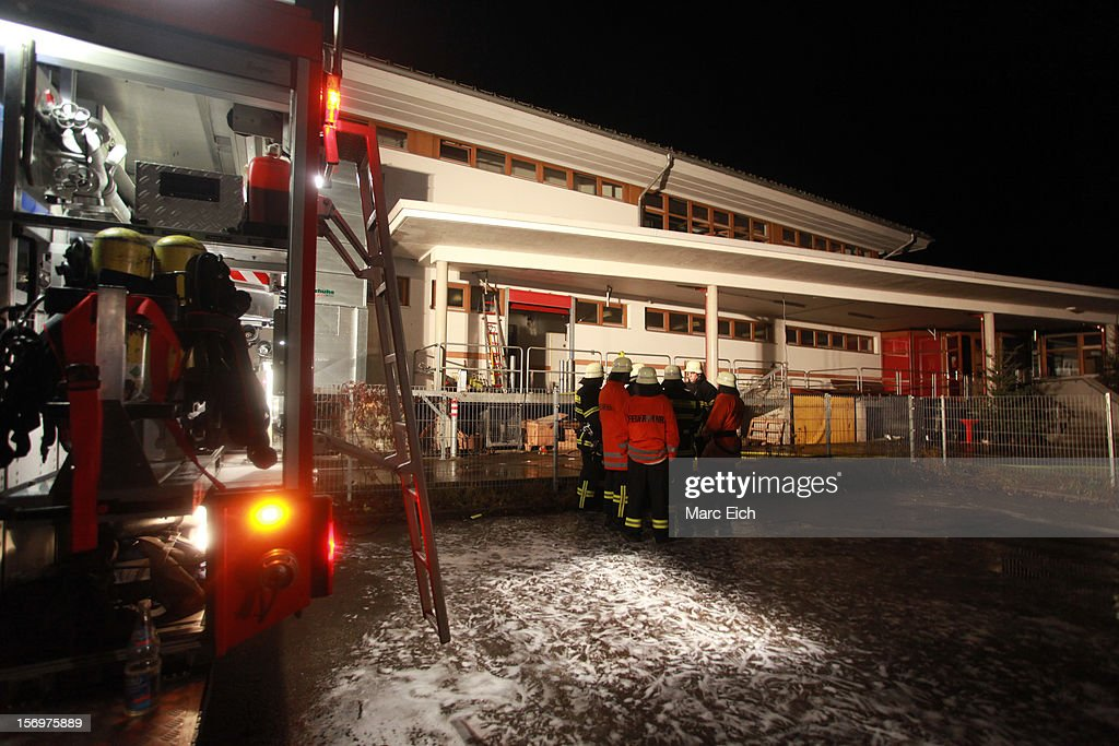 Firemen stand outside a Caritas employment facility for the handicapped in which 14 people died in a fire on November 26, 2012 in Titisee-Neustadt, Germany. The fire was reportedly caused by an explosion at the facility, where approximately 120 people with disabilities are employed in light manufacturing.