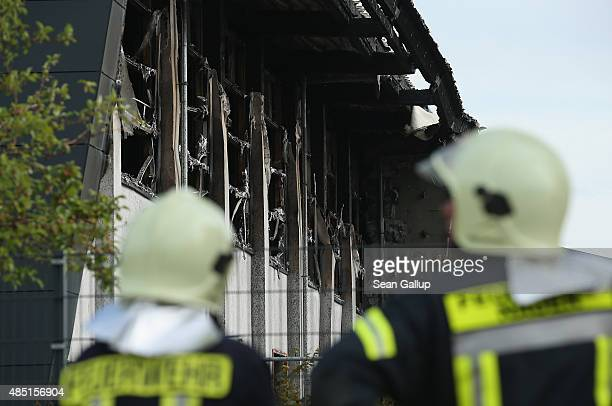 Firemen stand outside a sports hall struck by fire that was intended to house refugees and migrants applying for aslyum in Germany on August 25 2015...