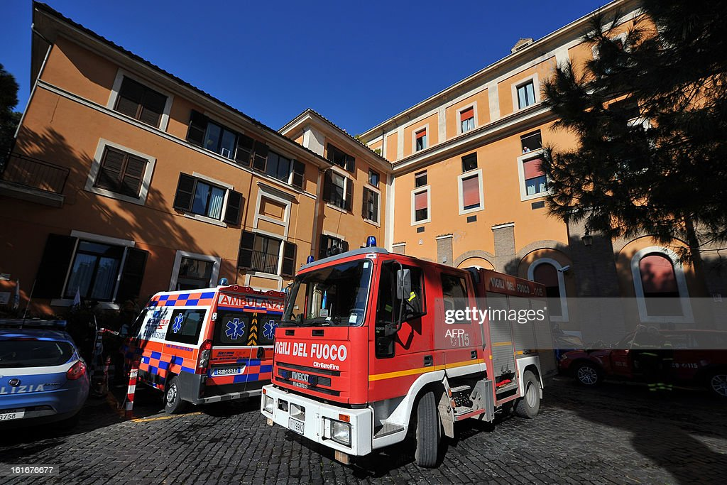 Firemen stand outside the Fatebene Fratelli hospital on the Tiberina island in Rome on February 14, 2013. The fire started in the department of psychiatry. AFP PHOTO / TIZIANA FABI