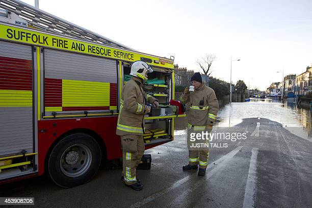 Firemen stop for a cup of tea after a night working in flooded streets in Lowestoft in the east of England on December 6 2013 after a tidal surge hit...