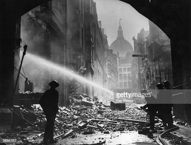 AFS firemen tackle a blitz fire amidst the rubble surrounding St Paul's Cathedral London