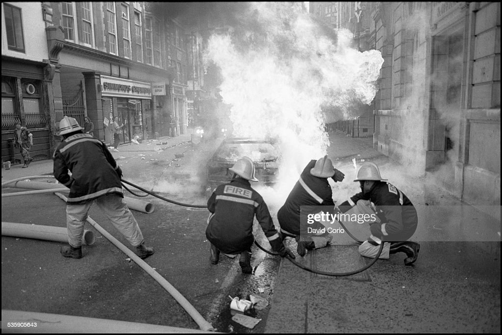 Firemen tackle a burning car during the Poll Tax demonstration in the West End of London, UK, 31st March 1990.