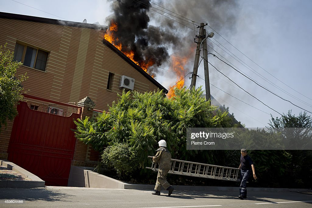 Firemen try to put out a fire in a residential area of Donetsk, named Voroshyloskyi after it was hit by artillery shelling on August 14, 2014 in Donestk, Ukraine. A Russian aid convoy is on its way towards the Ukranian border, heading to a crossing controlled by pro-Russian rebels instead of a government controlled post which the Ukrainian government has demanded it head to, according to the latest reports. The government has threatened to block the convoy if the cargo could not be inspected and is sending its own cargo of aid to the war-torn region of Luhansk.