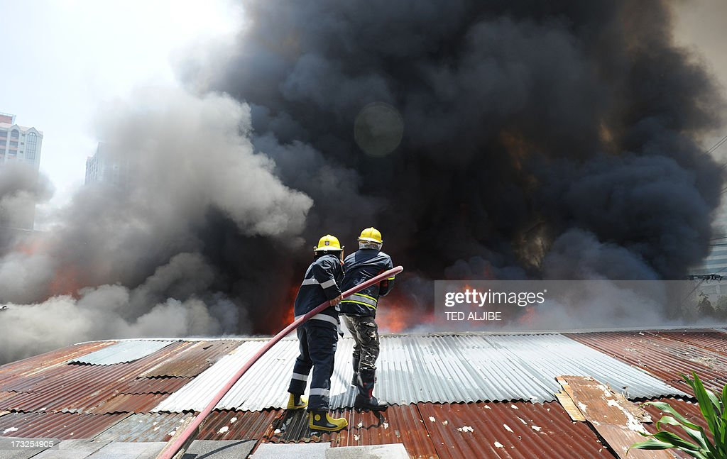 Firemen use hose water to fight a fire as it engulfs a shanty town at the financial district of Manila on July 11, 2013, leaving more than 1,000 people homeless according to city officials. There were no immediate reports of casualties from the blaze, which occurred mid-morning amid government plans to relocate thousands of families living in areas vulnerable to floods and typhoons.