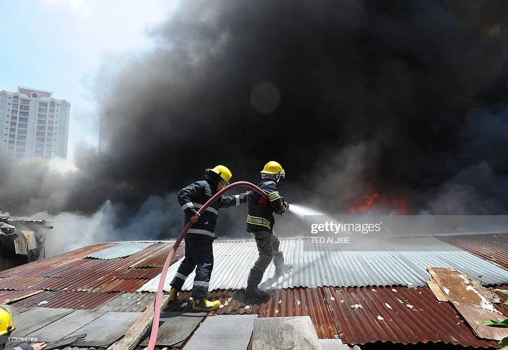 Firemen use hoses to fight a fire as it engulfs a shanty town at the financial district of Manila on July 11, 2013, leaving more than 1,000 people homeless according to city officials. There were no immediate reports of casualties from the blaze, which occurred mid-morning amid government plans to relocate thousands of families living in areas vulnerable to floods and typhoons.