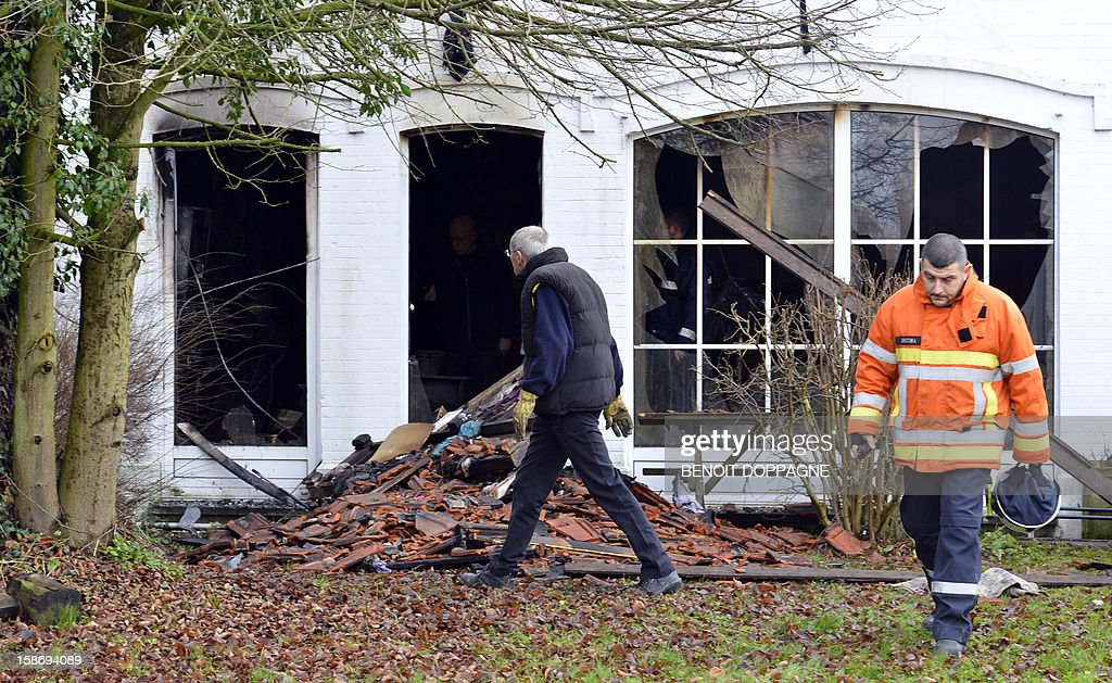 Firemen walk at the scene of a house fire in Hanzinne, Florennes on December 24, 2012 after a blaze brokeout around 4am killing a woman and her child and injuring a man and three other children. AFP PHOTO / BELGA PHOTO BENOIT DOPPAGNE