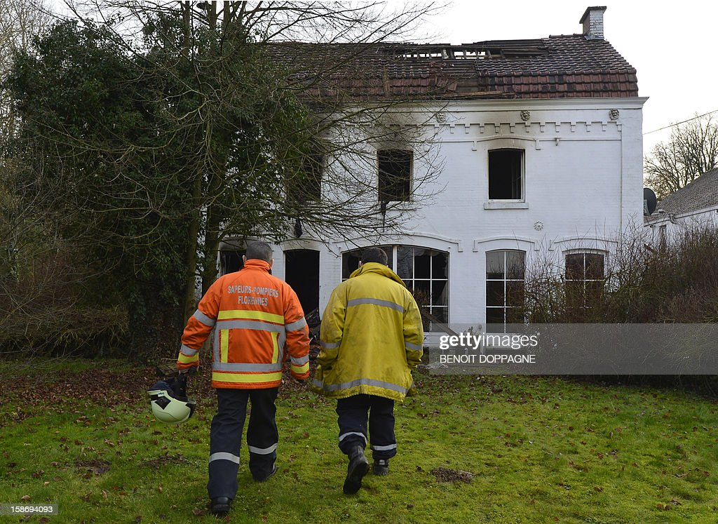 Firemen walk at the scene of a house fire in Hanzinne, Florennes on December 24, 2012 after a blaze brokeout around 4am killing a woman and her child and injuring a man and three other children.