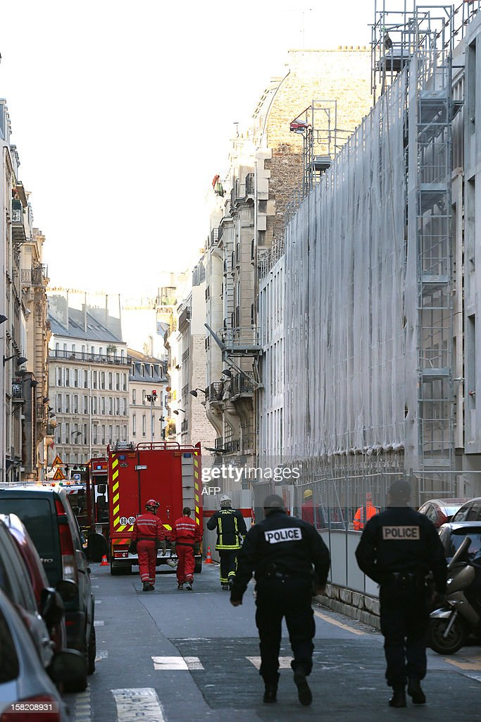 Firemen walk near the Laennec hospital, on December 11, 2012 in Paris, after the roof of an old building being renovated collapsed, seriously wounding two people working on the renovation site.