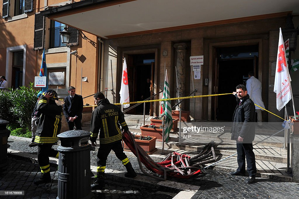 Firemen walk outside the Fatebene Fratelli hospital on the Tiberina island in Rome on February 14, 2013. The fire started in the department of psychiatry. AFP PHOTO / TIZIANA FABI