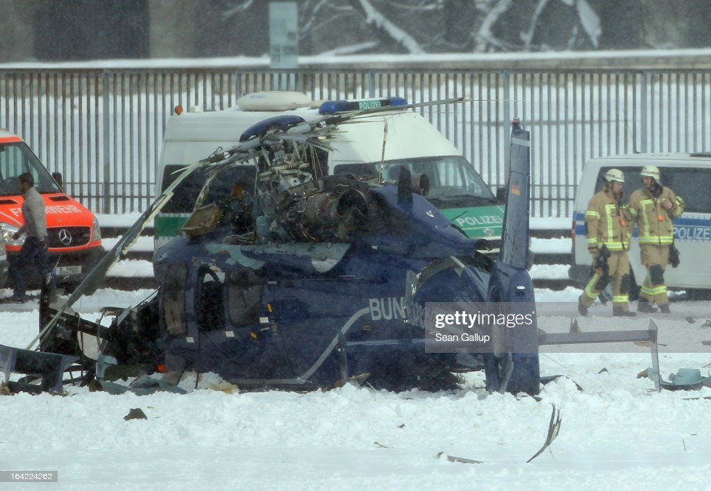 Firemen walk past the wreckage of one of two police helicopters that collided near the Olympiastadion stadium, killing one pilot and leaving several injured, on March 21, 2013 in Berlin, Germany. The helicopters were partcipating in a police exercise meant to simulate football hooligan clashes with police when the accident occured.