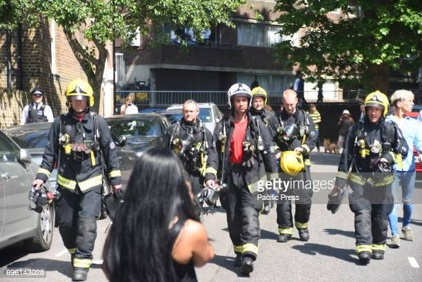 Firemen walking towards the fire site Smoke and flames billows from Grenfell Tower as firefighters attempt to control a blaze at a residential block...