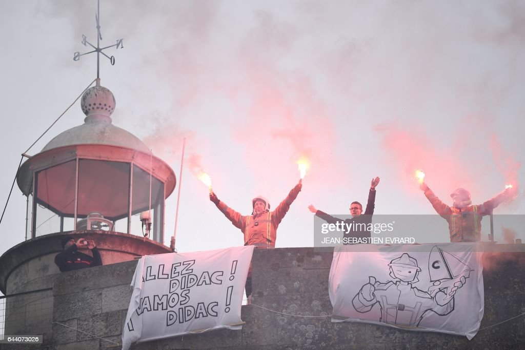 TOPSHOT - Firemen wave flares to celebrate the arrival of Spanish skipper and fireman Didac Costa at the end of the Vendee Globe around-the-world solo sailing race on February 23, 2017 in Les Sables-d'Olonne, western France. Costa, who was taking part in the race for the first time, finished 14th. /
