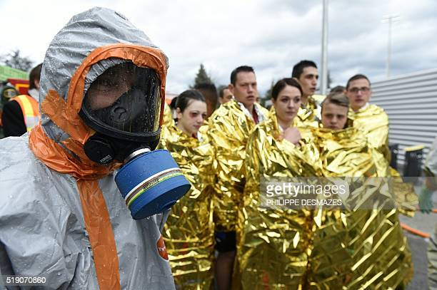 Firemen wearing chemical protective clothing attend to 'victims' during a chemical attack mock exercice on April 4 2016 at the Geoffroy Guichard...
