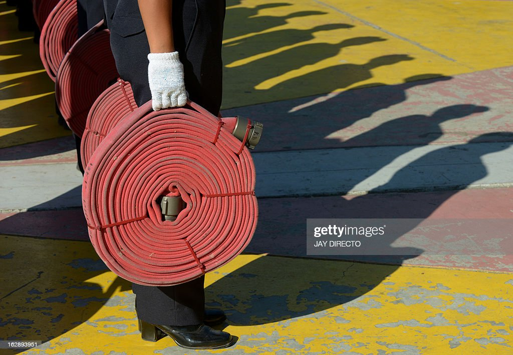 Firemen with water hoses join in a ceremony in Manila on March 1, 2013. The Bureau of Fire and Protection encourage everyone to join in the observance of the 47th Fire Prevention Month during a kick-off ceremony at Quezon Memorial Circle. AFP PHOTO / Jay DIRECTO.