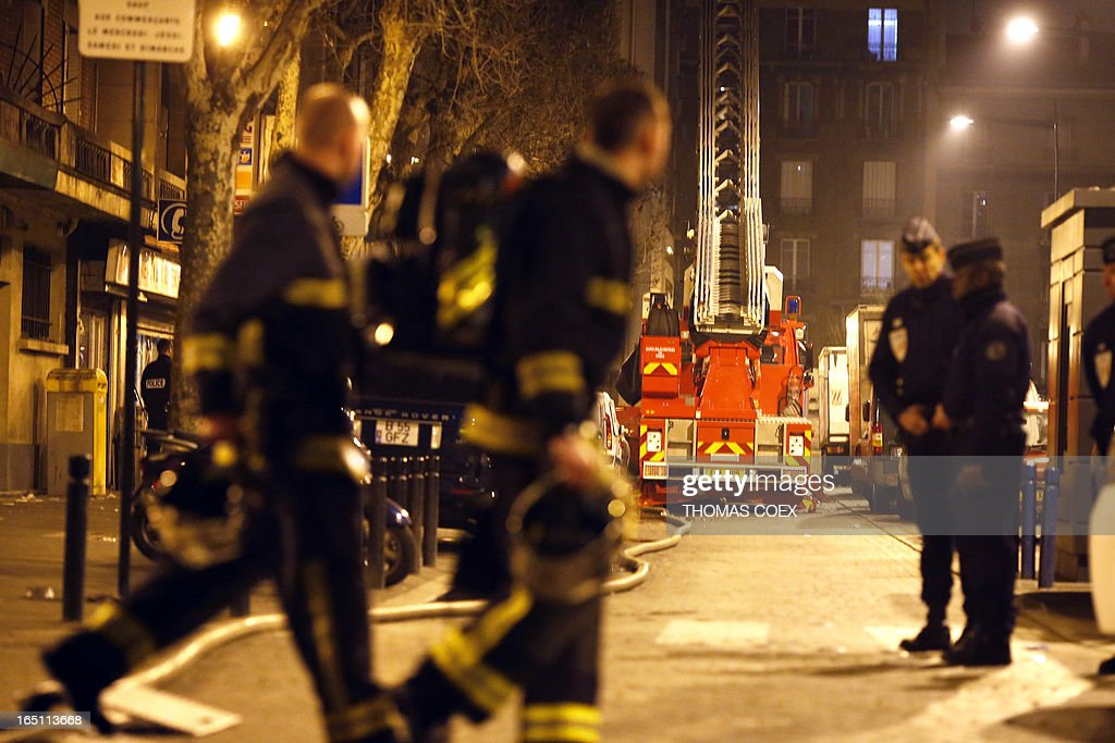 Firemen woark at the site of a building that was gutted by fire in Aubervilliers, a suburb of Paris, on March 30, 2013. Two people were killed and five other were seriously injured in the fire.
