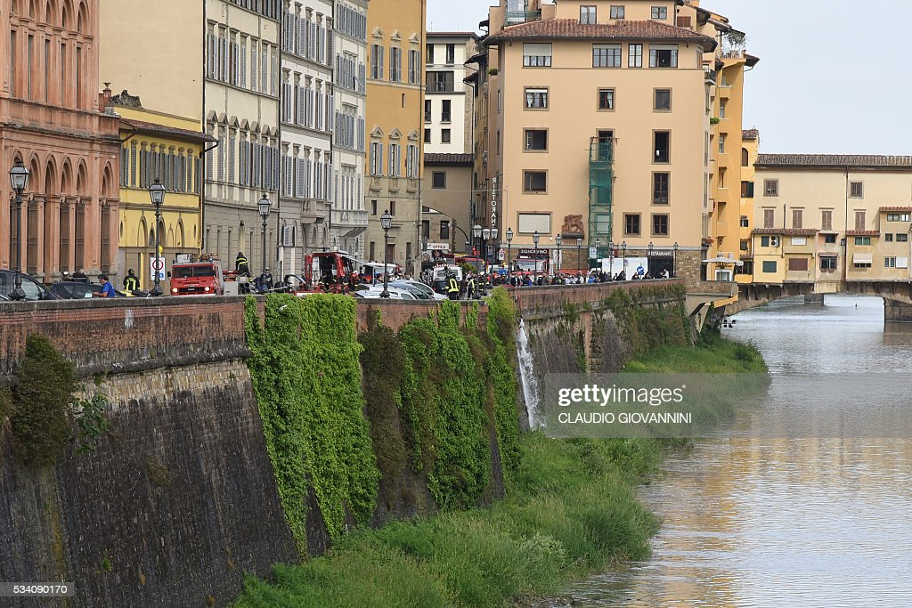 Firemen work along the Arno river where a collapsing of two hundred meters by seven wide occured early on May 25, 2016 on Lungarno Torrigiani in central Florence between Ponte Vecchio and Ponte alle Grazie. The collapse could be due to the rupture of a large water pipe firemen said. / AFP / CLAUDIO