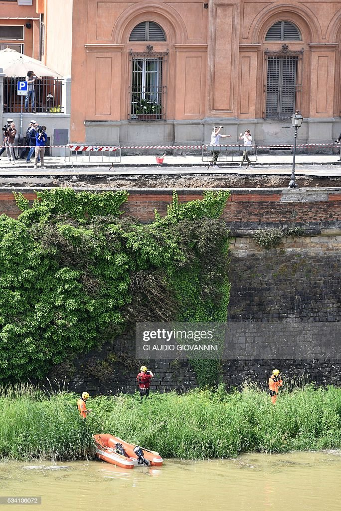 Firemen work along the Arno river where the embankment running alongside the Arno river collapsed early on May 25, 2016 in central Florence. The damage, stretching between the 14th century Ponte Vecchio and the Ponte alle Grazie, affected about 200 metres of the embankment in total. Emergency services said the collapse was due to a water pipe break and authorities stopped traffic along the road. / AFP / CLAUDIO