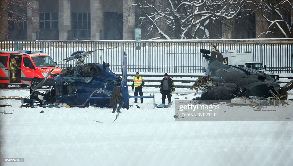 Firemen work at the scene where two police helicopters crashed near the Olympic stadium in Berlin on March 21, 2103. The helicopters crashed as they were landing after a training exercise.