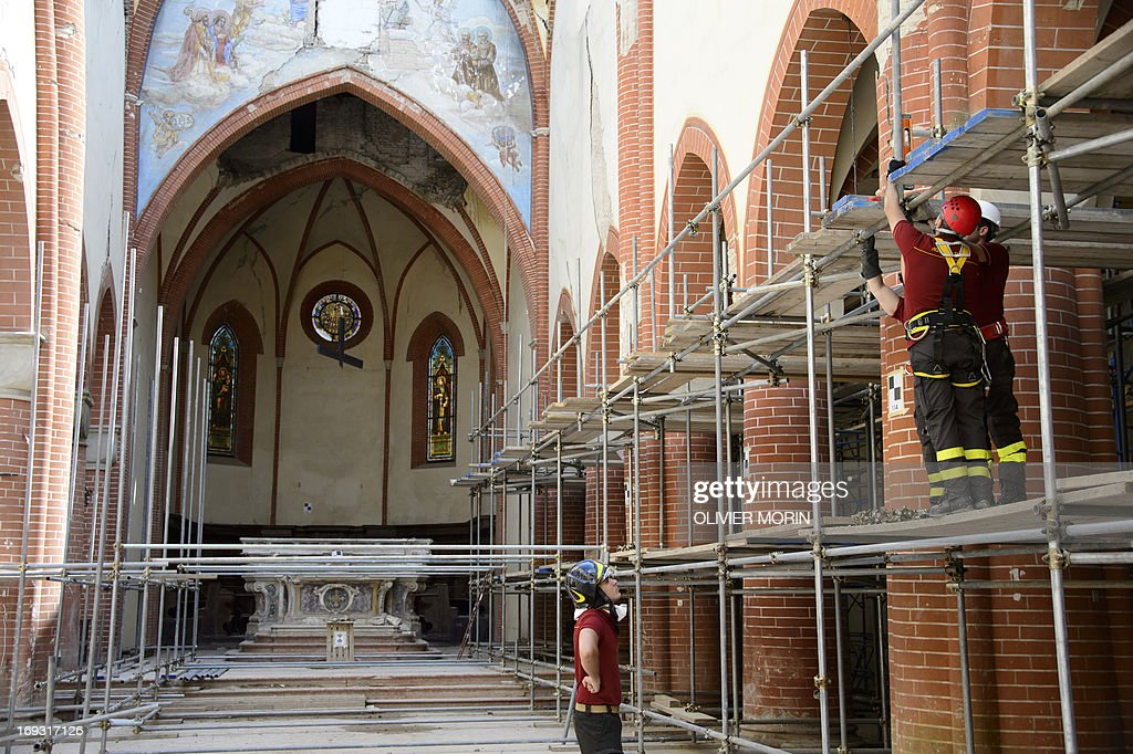 Firemen work in the damaged church (duomo) in Mirandola on May 22, 2013 a year after an earthquake in the Emilia Romagna. Reconstruction efforts in Emilia Romagna in Italy are proceeding slowly a year after two powerful earthquakes wrecked homes and businesses in this rich farming and medical industry region.