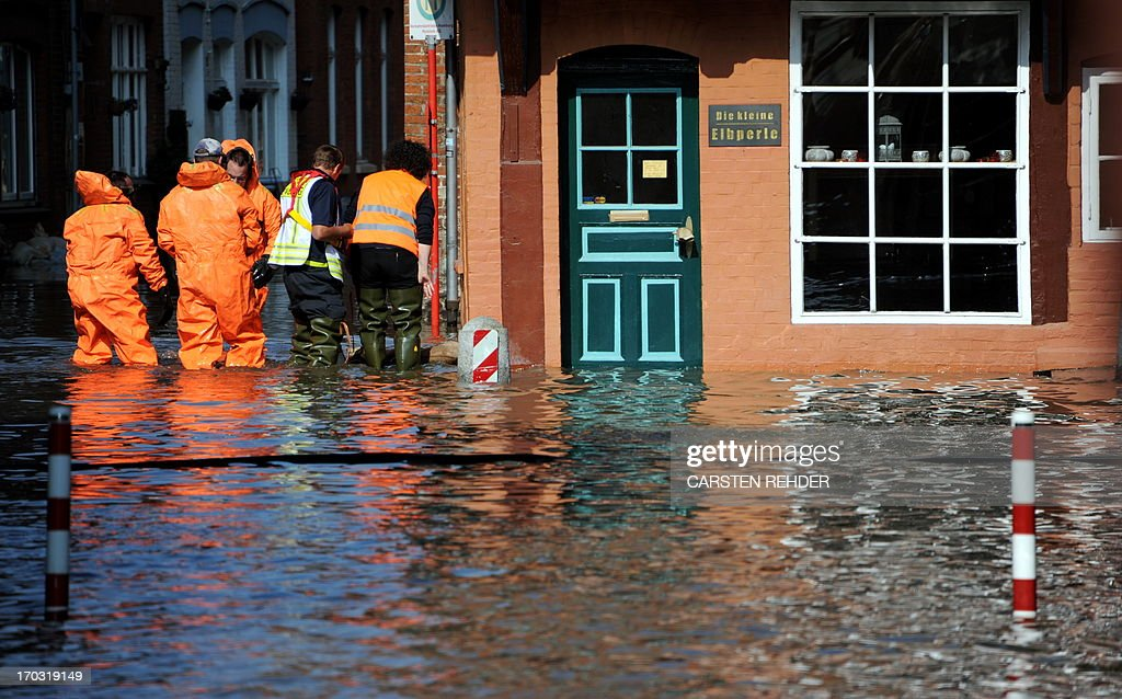 Firemen work in the old town of Lauenburg, northern Germany, flooded by the river Elbe on June 11, 2013. Deadly floods forging a path of devastation through central Europe for more than a week bore down on northern Germany as troops raced to bolster sodden dykes. AFP PHOTO / CARSTEN REHDER / GERMANY OUT