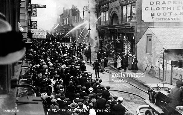 Firemen working to control a fire at commercial premises in Union Street Aldershot circa 1910