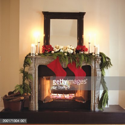 Fireplace decorated with Christmas stockings and Poinsettias : Stock Photo