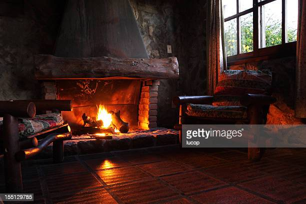 Cheminée avec bûches en bois, de chaises et de fenêtre