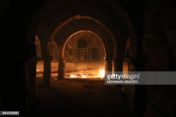 CORRECTION Fires burn inside the Omari Mosque billows following a reported air strike on a rebelheld area in the southern Syrian city of Daraa early...