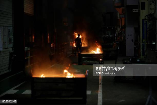 Fires set by employees are seen inside the plant of the GMS company on June 27 2017 in La Souterraine central France Around 280 jobs are on the line...
