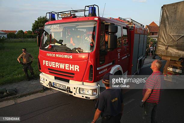 A firetruck makes its way through a street clogged with trucks delivering sandbags as Bundeswehr soldiers and local volunteers scramble to protect...