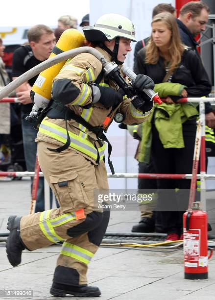 A firewoman runs with a fire hose during the 6th Firefighter Combat Challenge on September 8 2012 in Berlin Germany The Firefighter Combat Challenge...