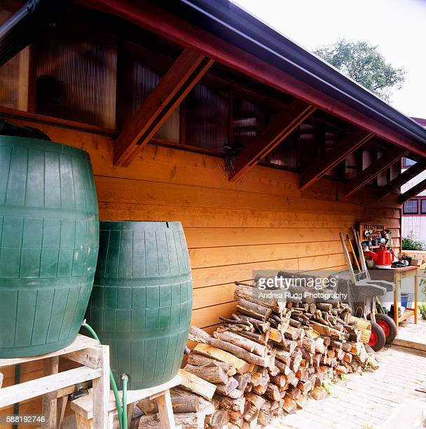 Firewood and Plastic Barrels Next to Garage